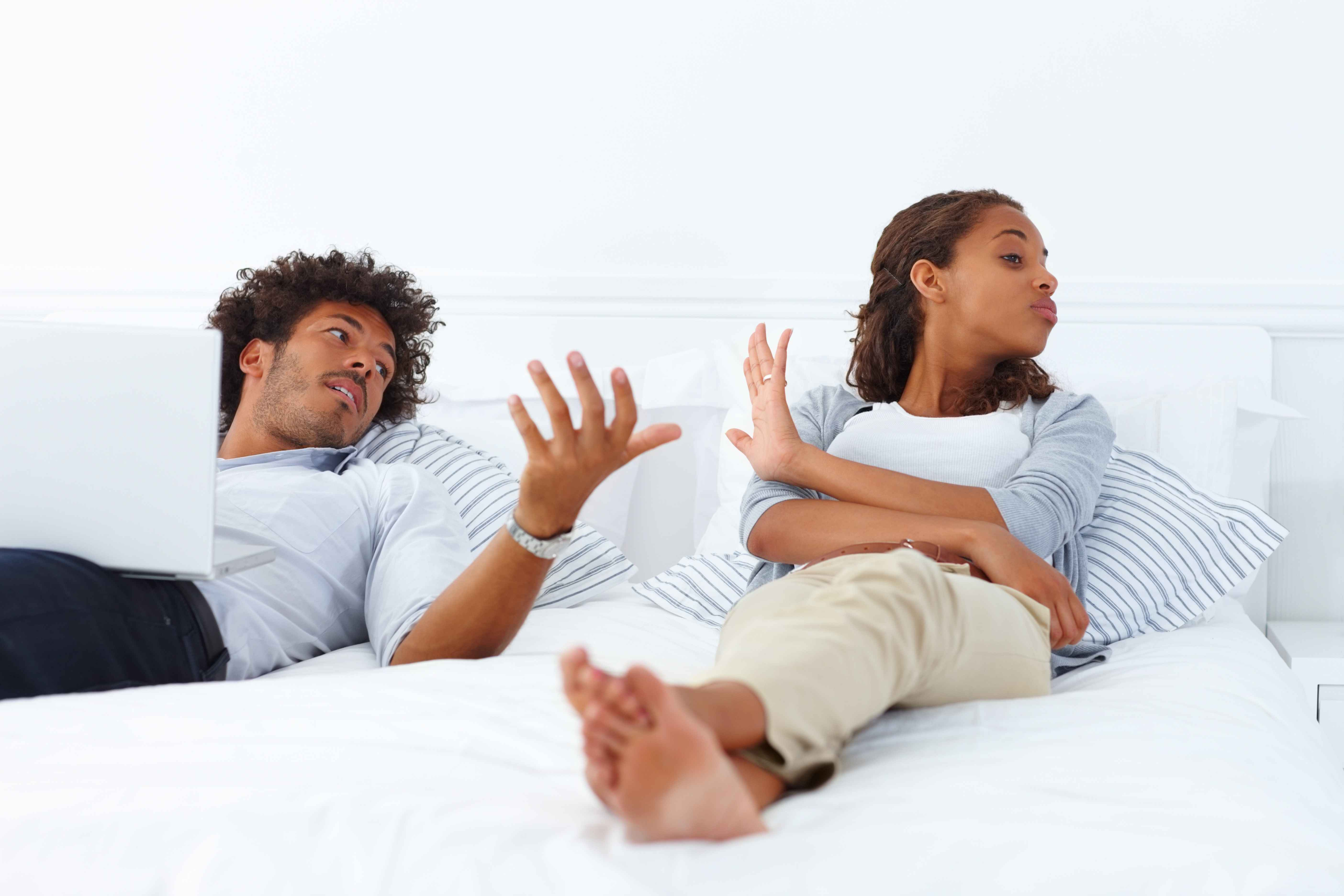 Portrait of a young unhappy African American couple lying on the bed and arguing